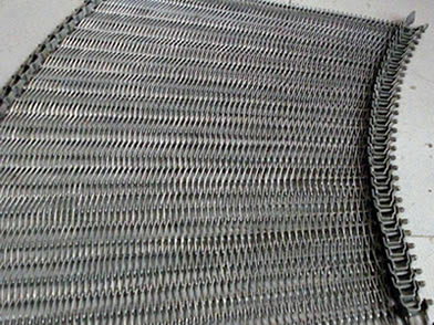 A curved balanced weave conveyor belt on the ground.