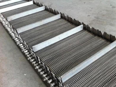 A compound weave conveyor belt with side guards and baffles on the ground.