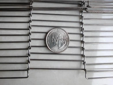 A part of ladder shaped conveyor belt with a metal coin on its surface.