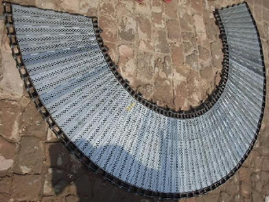 A curved perforated plate conveyor belt on the ground.