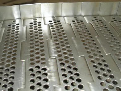 A stainless steel perforated plate conveyor belt with side guards on the ground.