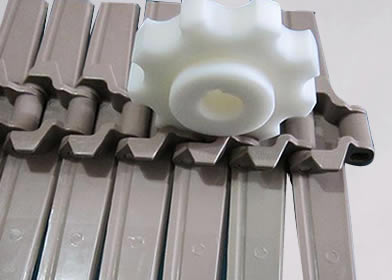 A plastic sprocket wheel on the track of plastic chain plate conveyor belt.