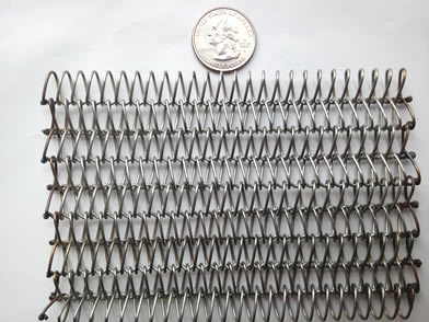 A piece of balanced weave metal conveyor belt with welded edge is beside a metal coin.